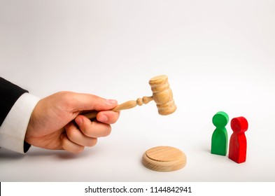 The referee's hand holds a hammer and issues a verdict in the dispute between the red and green opponents. court cases, the resolution of disputes and charges between the defendant and the plaintiff.