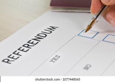 Referendum ballot paper, black pen, and passport on the table. Closeup