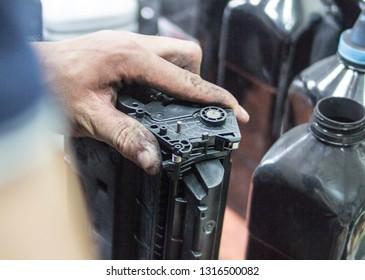 Refill printer cartridge. Hand holding printer cartridge