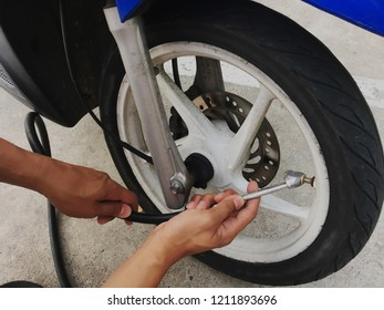 Refilling air into motorcycle tire at petrol station.