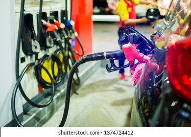 refilling the car with fuel at the gas  station and blurry staff background, black car in gas station, refilling the car with fuel at the refuel station, the concept of fuel energy, selective focus.
