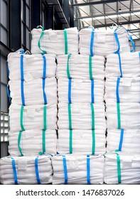 Refine sugar in white jumbo bag stack inside warehouse.