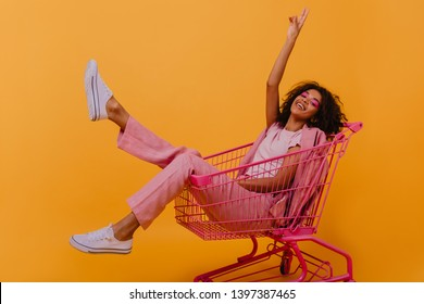 Refined african girl in pink costume having fun in studio. Relaxed young lady lying in shopping cart.