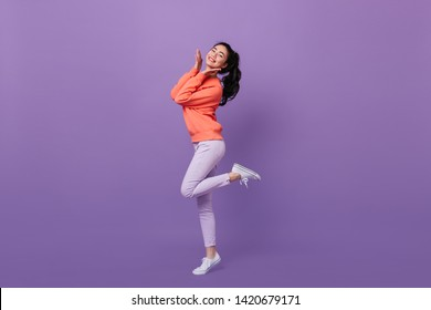 Refined asian woman standing on one leg. Full length view of blissful chinese girl dancing on purple background.