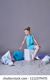 Refined beautiful little girl lady sits on cube,hand reaches,ball origami figure paper.Charming elegance.Romantic pretty child posing in designer blue dress,style for kids.Origami and minimalism.