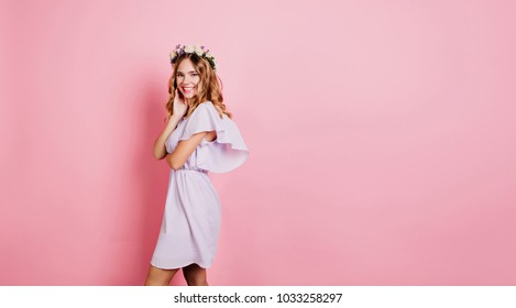 Refined blonde woman in summer dress standing near pink wall with smile. Place for text. Indoor portrait of positive girl in flower wreath enjoying photoshoot.