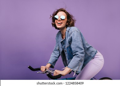 Refined female bicyclists enjoying photoshoot. Charming curly girl in denim jacket and sunglasses sitting on bike.