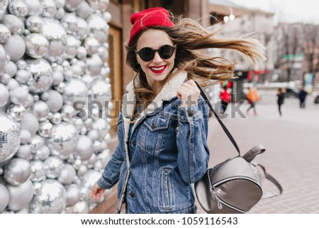 c4eca0b1a78f Refined girl in denim jacket posing with trendy backpack on street  background. Spectacular woman in
