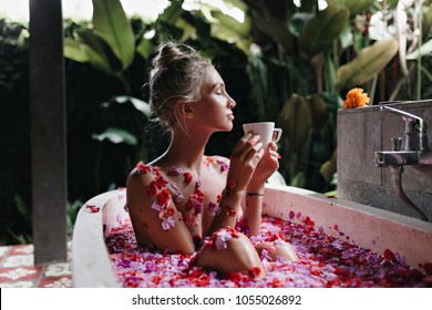 Refined girl sitting in bath on nature background. Wonderful caucasian lady relaxing during spa and drinking tea.