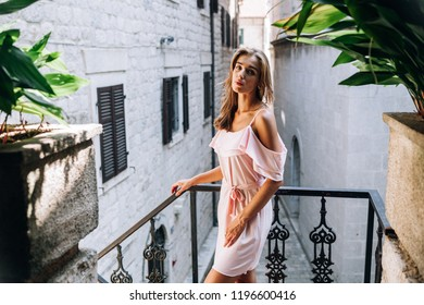 refined girl is standing on the balcony of a European city