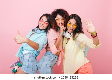 Refined hispanic woman in colorful bracelets waving hand during joint photoshoot with friends. Lovely asian lady in stylish blue shirt laughing while spending time with girls.