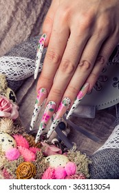Refined painted long nails and hands with flower symbol. Easter or wedding theme with wreath rose and eggs.