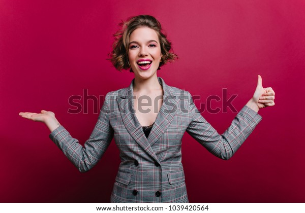 Refined pale girl with curly hairstyle posng on claret background after workday. Indoor portrait of graceful business-woman in gray jacket smiling in studio.