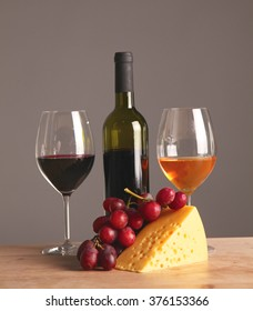 Refined still life of wine, cheese and grapes on wicker tray on wooden table