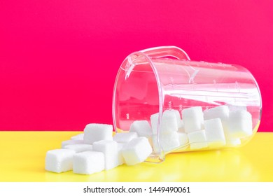 refined sugar on a bright pink and yellow background in a measuring glass.Lies on a side of and sugar to Wake up.the concept of the harms of simple carbohydrates,excessive consumption of sugar in food