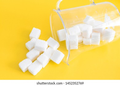 refined sugar on a bright yellow background in a measuring glass. Lies on a side of and sugar to Wake up. top view. concept of the harms of simple carbohydrates, excessive consumption of sugar in food