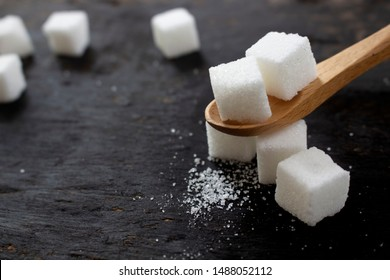 refined sugar or white sugar crystals placed on a wooden spoon Is a component of drinks, coffee, tea, desserts. For good health, must control eating