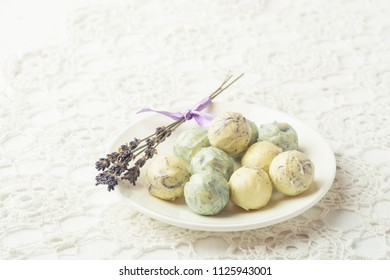 Refined sweets from white chocolate with a lavender taste on a white plate, on an openwork tablecloth. View from above. Flat layout. Place for design.Copy space