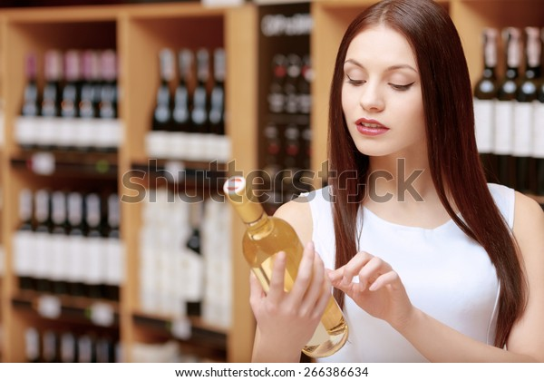 Refined taste. Close-up of a pretty young woman examining the bottle of white wine in a liquor store