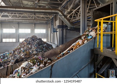 Refiner and chain stepped conveyor equipment of modern waste recycling plant transports waste from receiving department to sorting, recycling and disposal with copyspace.