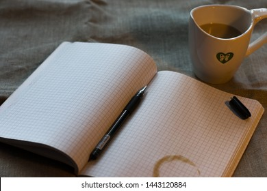 refiner from a cup of coffee on the notebook with open gel pen and cup of milk cofee on the flax background on the table ander the lump light