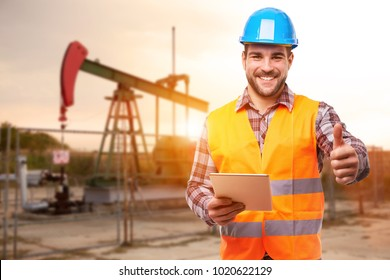 Refinery worker standing in front of the oil pump with thumb up