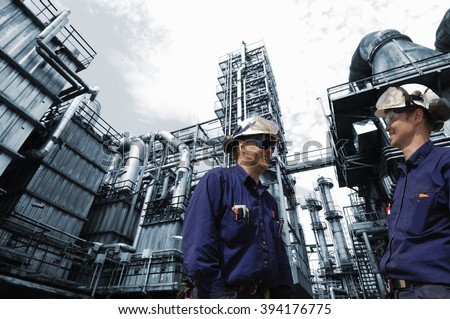 162c6c159a refinery workers in close-ups with large oil and gas industry in background