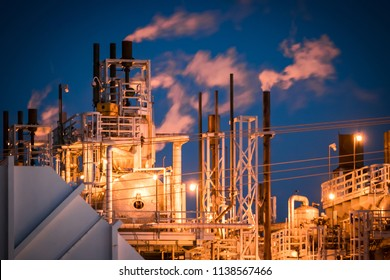 Refining facilities lighted in industrial glow, spewing exhaust into the the dark early morning skies.
