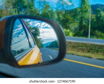 Reflect Perspective line of highway road on car mirror while driving use for car insurance business concept
