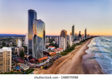 Reflecting facets of modern urban high-rise towers on Australian Gold Coast in Queensland Surfers Paradise. Wide sandy long beach of Pacific shore at sunrise in elevated aerial view along waterfront. - Shutterstock ID 1488970988