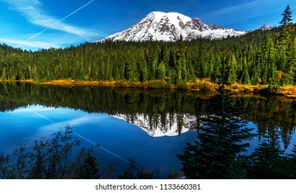 Reflection of an aircraft contrail on an early autum morning at Reflection Lake, Mt. Rainier.