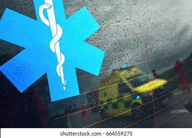Reflection of the ambulance car. Teams of the Emergency medical service are responding to an traffic accident in bad weather.