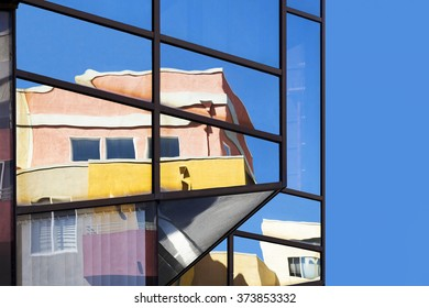 Reflection of apartments on a glass building.