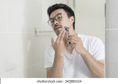 Reflection of a asian young man shaving in bathroom mirror