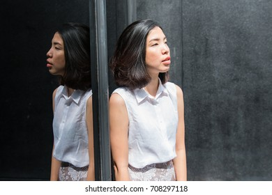 the reflection of asian young woman on the mirror in a sunny day