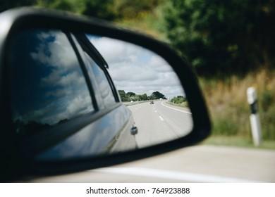 Reflection of asphalt highway road at the car side mirrow. Travel by car summer season