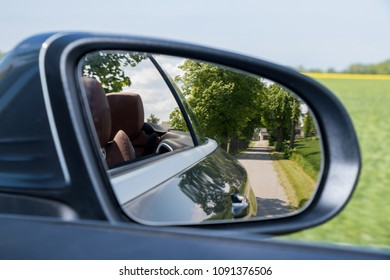 Reflection of asphalt highway road at the Convertible car side mirrow. Travel by Luxury Convertible Sports Car summer season