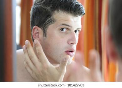 Reflection of an attractive man shaving in bathroom mirror