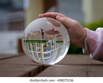 Reflection of a beautiful new home in a transparent bowl. child's hand. The child holds a ball. The concept of construction, new housing for young families Real Estate