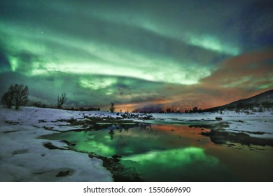 The reflection of the beautiful northern lights in the water at night captured in Norway