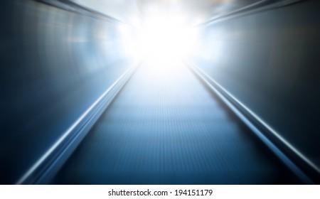 reflection of  blue moving escalator in underground train station.