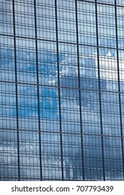 A reflection of a blue sky with clouds in the mirrored windows of a tall office building.