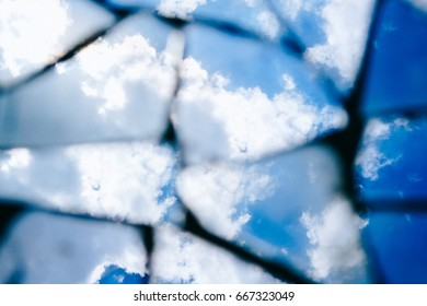 Reflection of a blue sky with fluffy clouds in dirty broken pieces of a mirror. Tinted stylish photo.