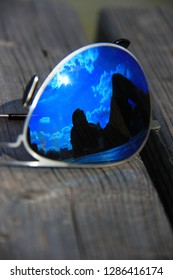 Reflection in blue sunglasses of a man chilling on a dock with a drink bottle beside him on a sunny day with some clouds, concept of chilling, relaxing