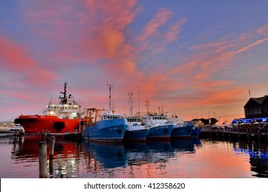 Reflection of boats and clouds on water at sunset time at Fremantle, Australia