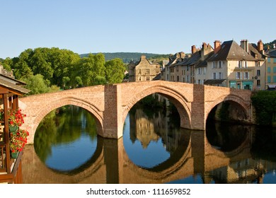Reflection of the bridge and Old Palace of Espalion in Aubrac, France