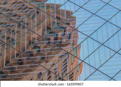 Reflection of a building on the glass panes of another building