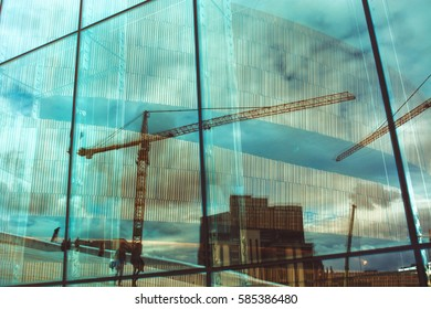 Reflection of buildings and cranes, clouds and walking people in large glass window