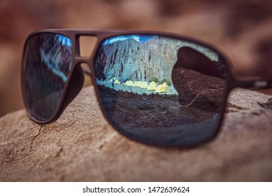 The reflection of the camping tents on a a pair of sunglasses