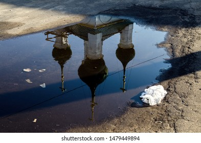 Reflection of a church in a puddle with garbage on a broken road in the center of Kostroma